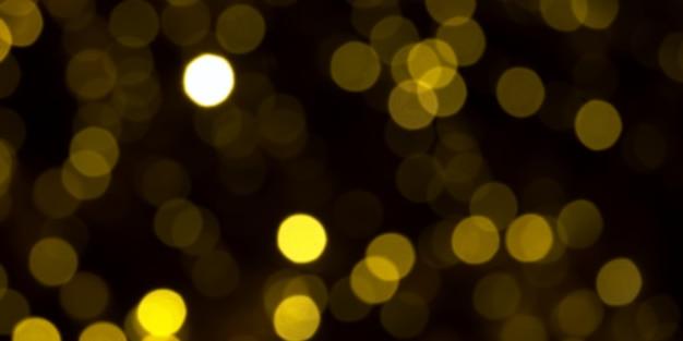 Luzes de natal douradas desfocadas em fundo escuro. círculos amarelos bokeh em fundo preto, fundo de natal
