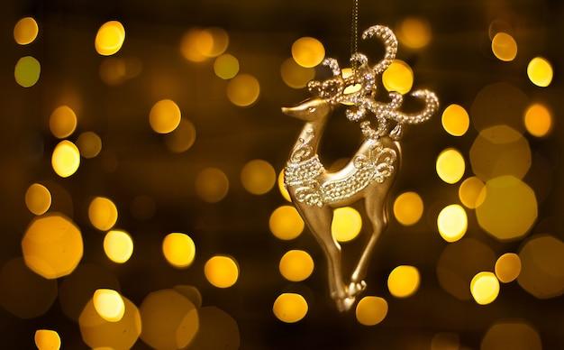 Luzes de natal douradas e cervo de brinquedo de natal
