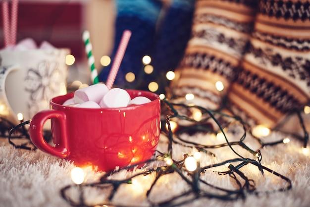Luzes de natal e caneca de chocolate com marshmallow no tapete