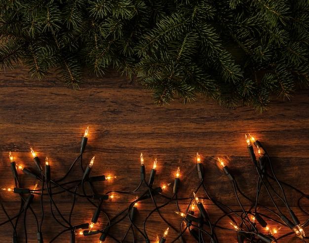 Luzes de natal e ramos de abeto em fundo de madeira
