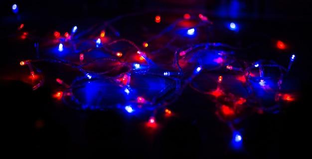 Luzes de natal em fundo escuro com espaço de cópia. guirlanda decorativa