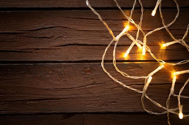 Luzes de natal em um antigo fundo de madeira texturizado