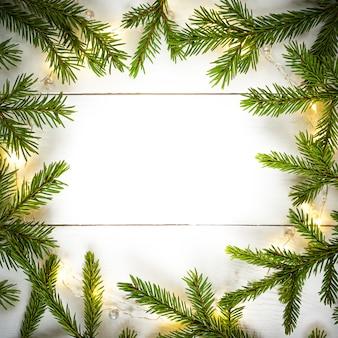 Luzes de natal guirlanda borda circular e ramos de abeto com espaço de cópia.
