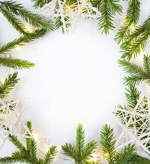 Luzes de natal guirlanda borda circular e ramos de abeto e estrelas brancas com espaço de cópia.