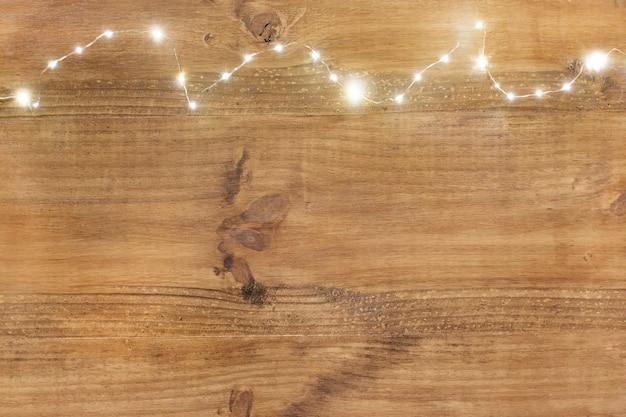 Luzes de natal na parte superior no fundo de madeira.