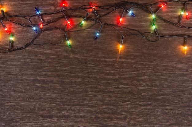 Luzes de natal no fundo escuro de madeira. feliz natal e feliz ano novo
