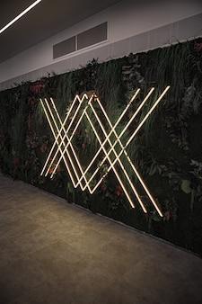 Luzes de néon na parede com plantas e flores