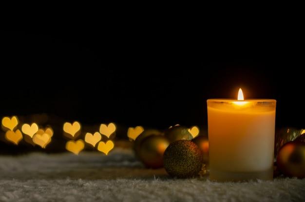 Luzes de velas e enfeites de natal com luzes de bokeh de forma de amor.