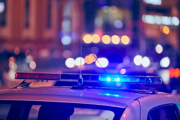 Luzes do carro de polícia na rua da cidade à noite. luzes vermelhas e azuis.