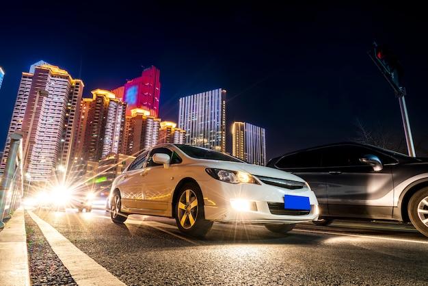 Luzes do carro turva e visões noturnas de paisagens arquitetônicas urbanas