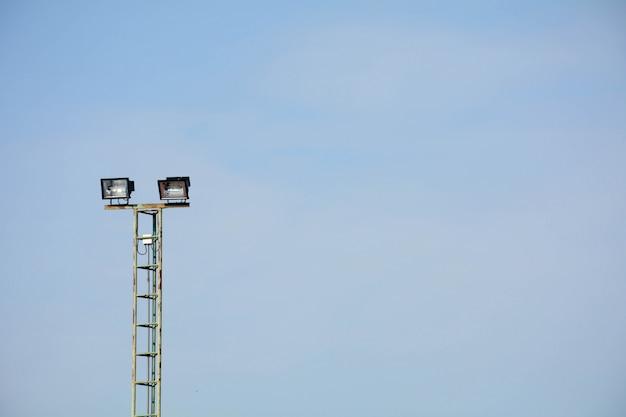 Luzes do estádio no campo de ténis no fundo do céu azul