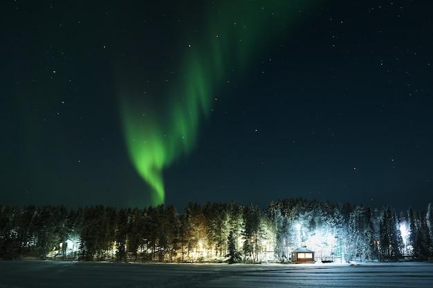 Luzes do norte sobre a floresta e casa