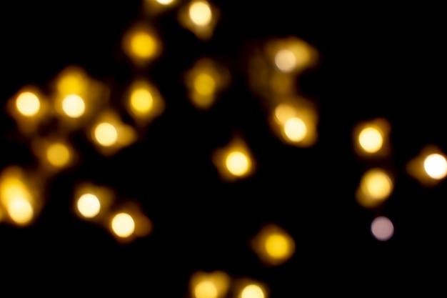 Luzes douradas do bokeh cintilando sobre fundo preto.
