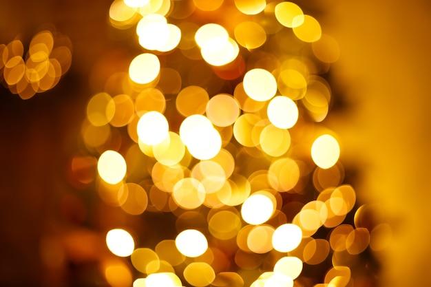 Luzes douradas festivas de guirlanda de natal e fundo desfocado