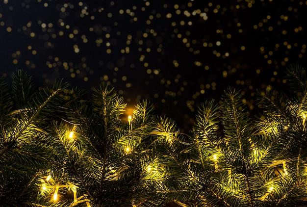 Luzes douradas na árvore de natal no fundo desfocado com brilhos no escuro