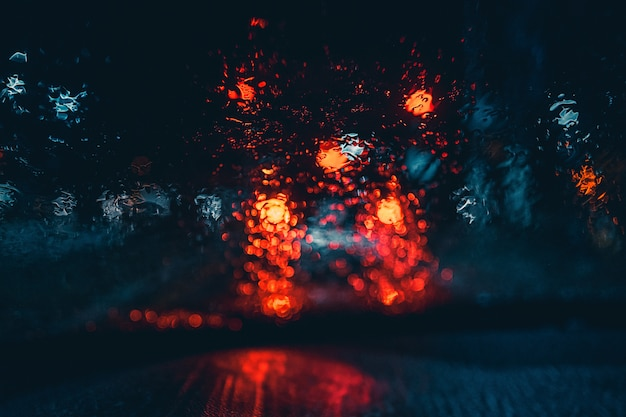 Luzes embaçadas do carro molhado de dentro de um carro