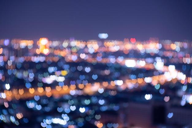 Luzes laranja, azuis e douradas desfocadas em forma de coração desfocaram o bokeh. fundo festivo de natal preto ou ano novo e dia dos namorados.
