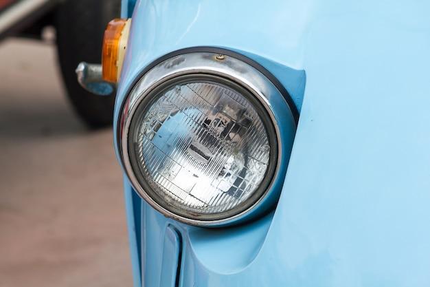 Luzes na frente de um carro antigo com uma esfera original.
