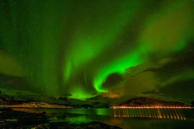 Luzes polares dramáticas, aurora boreal sobre as montanhas no norte da europa