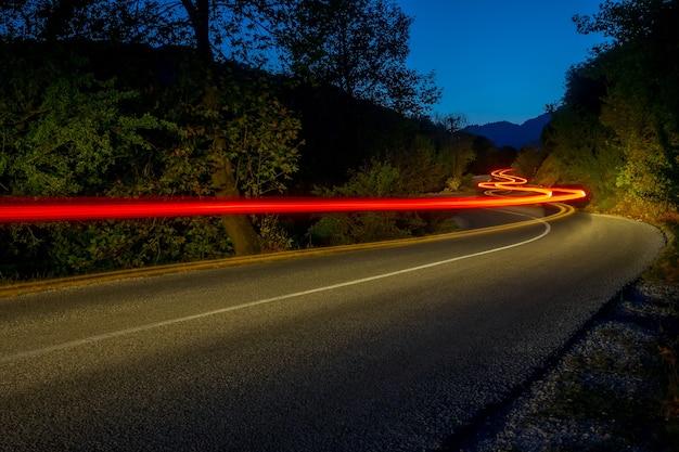 Luzes traseiras iluminam uma estrada vazia em uma floresta à noite de verão. trilhas longas e sinuosas