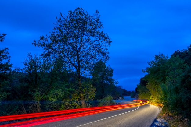 Luzes traseiras iluminam uma estrada vazia em uma floresta de verão à noite. trilhas longas e sinuosas