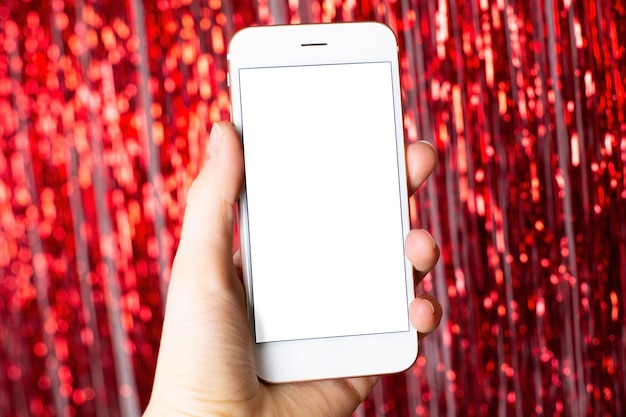 Luzes vermelhas e bokeh de natal. telefone inteligente na mão com tela isolada para apresentação de maquete, aplicativo ou web site