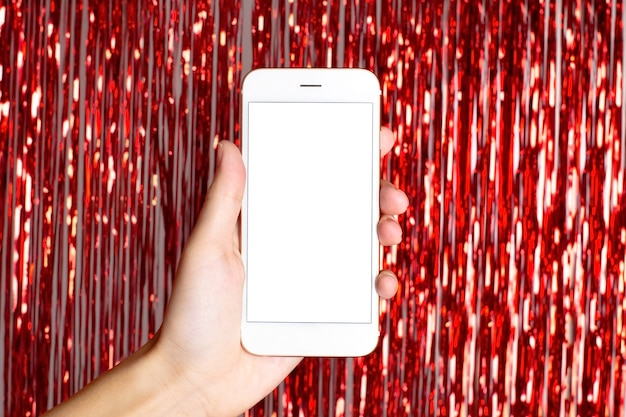 Luzes vermelhas e bokeh de natal. telefone inteligente na mão com tela isolada