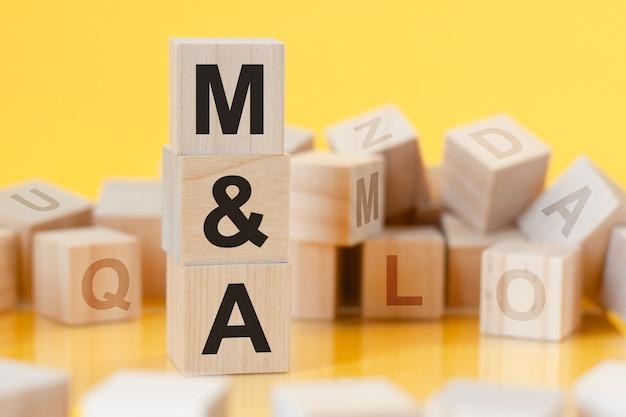 M e a - abreviação de fusões e aquisições - escrito em um cubo de madeira
