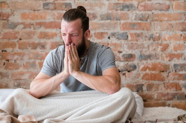 Má noite de sono. estresse e insônia. homem sentado na cama e bocejando muito. interior moderno do sotão. copie o espaço.