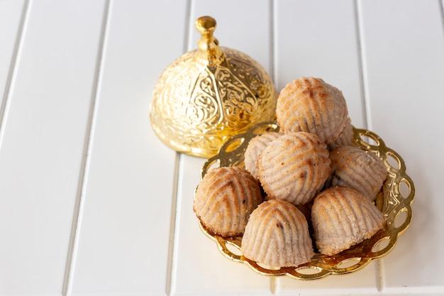Maamoul tradicional árabe preenchido pastelaria ou biscoito com tâmaras ou castanha de caju ou nozes ou amêndoa ou pistache. doces orientais. fechar-se. espaço de madeira branco.