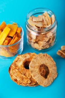 Maçã, abacaxi e manga chips em uma jarra e pedaços deste frutas sobre uma mesa