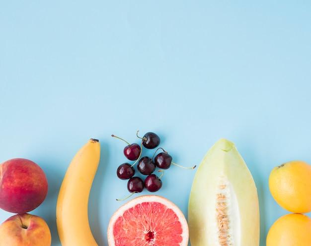 Maçã; banana; cerejas; toranja; muskmelon e limões em fundo azul