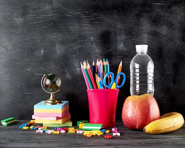 Maçã, banana, garrafa de água e papelaria para a escola
