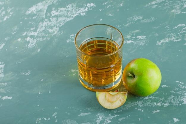 Maçã com fatia, bebida vista de alto ângulo em um fundo de gesso