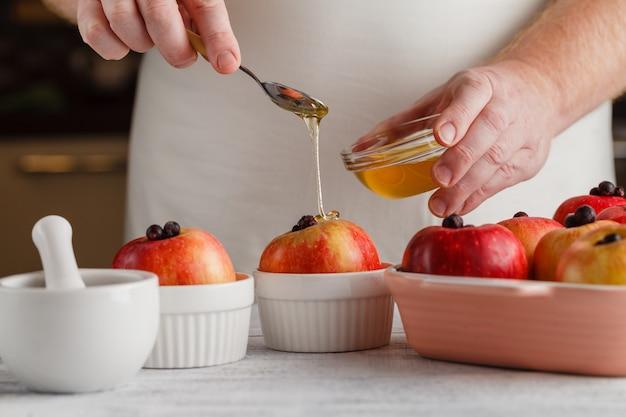 Maçã com ingredientes e mel sobre a mesa de madeira. foco seletivo