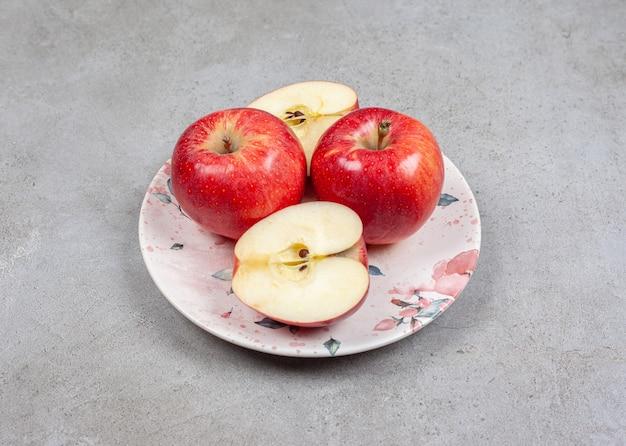 Maçã cortada ou inteira no prato. feche fotos de maçãs frescas.