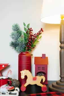 Maca de cavalo de madeira e galhos de abeto em uma lata de metal vermelha. decoração de natal em cores vermelhas