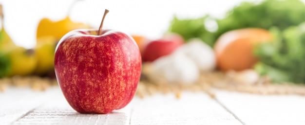 Maçã de gala saudável fresca na mesa de madeira branca, fundo panorâmico da bandeira