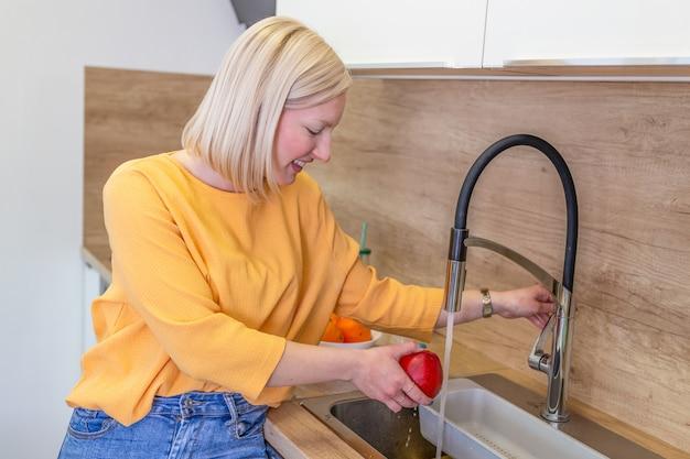 Maçã de lavagem da menina bonito na pia da cozinha. jovem mulher limpando sua fruta com água sob a torneira.