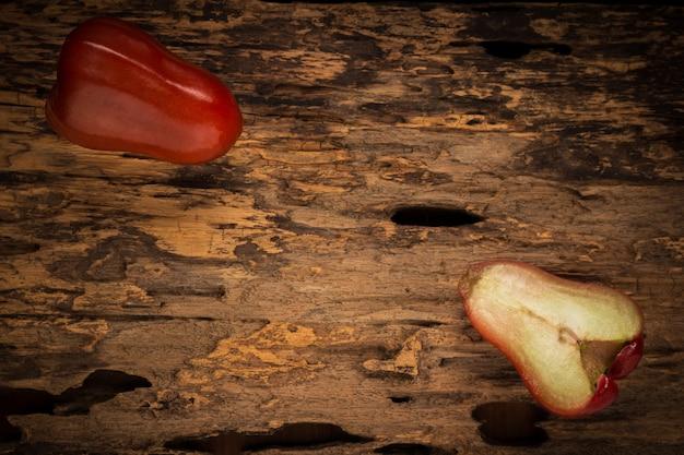 Maçã de rosa na madeira. sombrio. noite