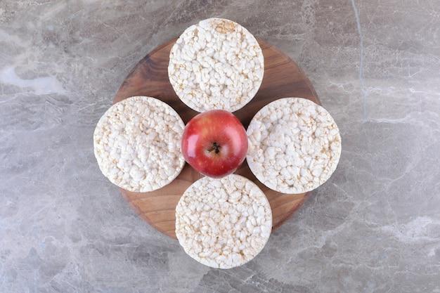 Maçã e bolinhos de arroz tufado na bandeja de madeira, sobre o fundo de mármore.
