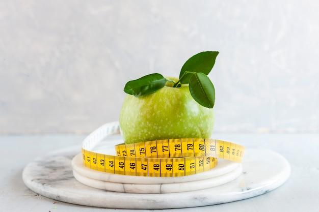 Maçã e centímetro verdes. frutas frescas, conceito para perda de peso, dieta, dieta cetogênica, jejum intermitente