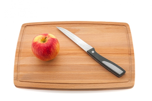 Maçã e faca suculentas vermelhas em uma placa de corte feita da madeira escura.