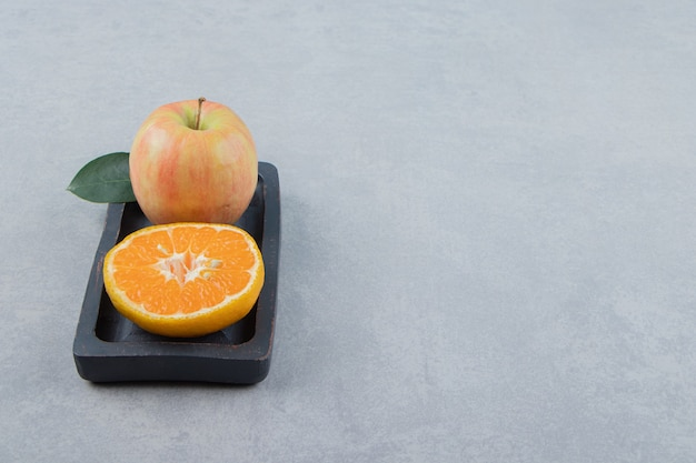 Maçã e fatia de laranja na placa preta