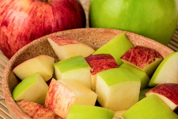 Maçã e frutas cortadas no fundo da natureza.