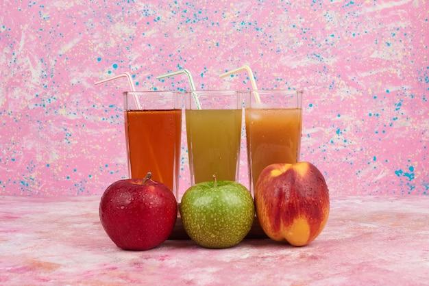 Maçã e pêssegos com copos coloridos de suco.