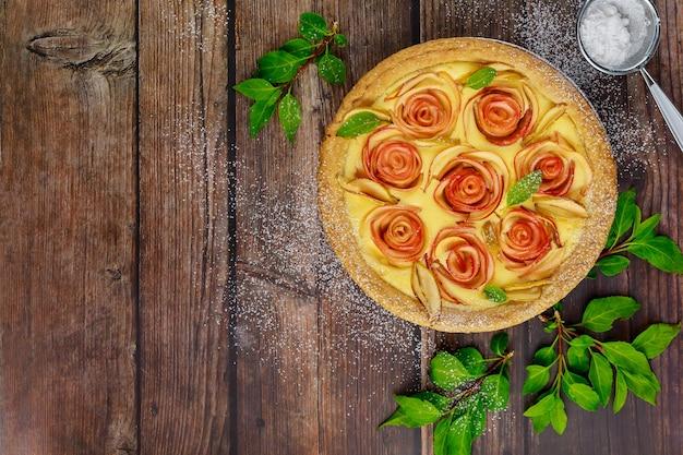 Maçã em forma de rosas na torta na mesa de madeira rústica.