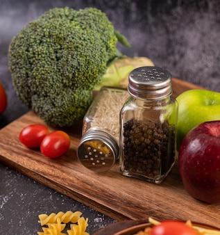 Maçã em uma placa de madeira com um frasco de sementes de pimenta