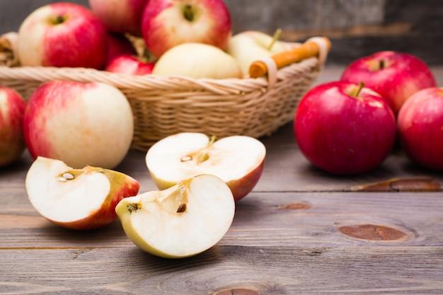 Maçã fatiada e maçãs vermelhas maduras em uma mesa de madeira e em uma cesta