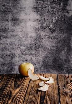 Maçã fresca e fatias de maçã seca em uma mesa de madeira